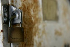 Padlock on rusty door. Macro shot of metal padlock and rusty door Royalty Free Stock Photos