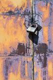 Padlock on rusty iron door Stock Images