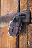 Padlock. Rusty padlock on wooden door stock photo
