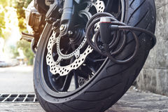 Padlock security lock blocking the motorcycle wheel on street, anti-theft system Stock Images