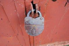 Padlock security organization red door. Padlock metal steel close-up red door security protection stock image