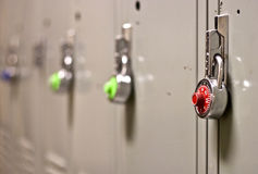 Padlock Security on a School Locker. A row of multi-colored pad locks on a row of lockers Stock Image