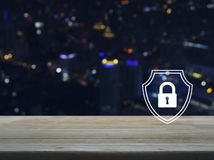 Business security insurance concept. Padlock with shield flat icon on wooden table over blur colorful night light city tower and skyscraper, Business security stock photos