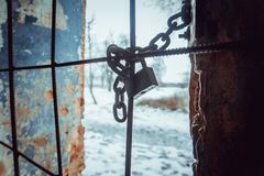 Padlock and sturdy steel chain wrapped around metal rods on window royalty free stock images