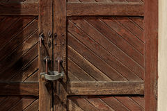 Padlock on a wooden door in a railway station in Italy. Old wooden door with padlock in a railway station Royalty Free Stock Photo