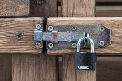 Padlock on wooden gate. Latches are screwed on the screws Royalty Free Stock Images