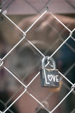 Padlock with the word love. Closed padlock on a fence with the word love Royalty Free Stock Photos