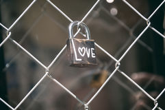 Padlock with the word love. Closed padlock on a fence with the word love Stock Photos
