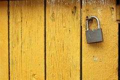 Padlock on yellow wooden door Royalty Free Stock Photo