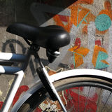 A Padlocked Bicycle Against a Graffiti Painted Wall Stock Photography