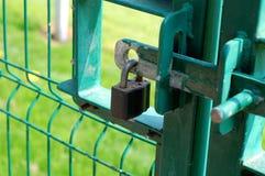 Padlocked Gate. Padlock locking a wire mesh security gate Royalty Free Stock Photo