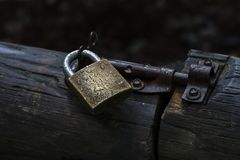 Padlock and bolt securing an old wooden gate Stock Photos