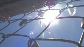 Padlocks и ленты на сетке утюга на предпосылке неба и солнца акции видеоматериалы