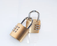 Padlocks. Two small padlocks hooked on white background Stock Photography