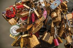 Padlocks fastened to each other celebrating love on pole over bridge at the Seine River in Paris. stock photography