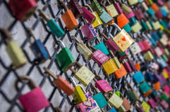Padlocks on Fence as Love symbol. Colorful padlocks with names and dates incribed represent love on a fence Royalty Free Stock Photography
