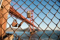 Padlocks and fence and the Golden Gate Bridge in the background at Fort Point, San Francisco stock photography