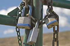 Padlocks, Gates and Chains. The rusted chain and padlocks on the rusty gate still prevent entry Royalty Free Stock Photography