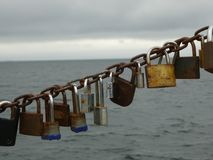 Padlocks pinned to the chain and Baltic Sea. Padlocks pinned to the chain at the pier in Sopot. The pier in Sopot is the longest wooden pier in Europe. /Baltic stock photography