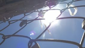 Padlocks and ribbons on iron mesh on sky and sun background. Love padlocks and ribbons left on the metal wire mesh, view against the sky with bright sunshine stock video footage