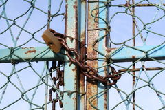 Padlocks and rusted chains secure gate at industrial site Stock Photo