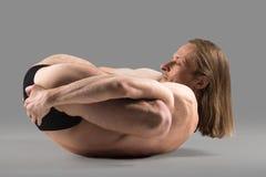 Padma yoganidrasana pose. Sporty muscular young yogi man lying in Padma yoganidrasana pose, (variation of Yogic Sleep Posture), studio shot on dark background Stock Photos