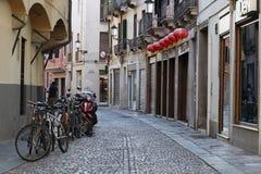 Padova, Italia - 24 agosto 2017: Le biciclette ed i motorini di motore hanno parcheggiato in una via calma Fotografia Stock