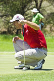Padraig Harrington. Putter in hand, kneeling down taking aim for his put, with a marshal blurred in the background Stock Photos