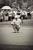Padraig Harrington. Putter in hand, aiming for his putt toward the hole, on the 1st green Stock Image