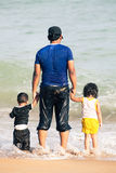 Padre árabe con dos niños que llevan a cabo las manos por el mar Fotos de archivo
