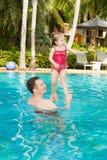 Padre activo que enseña a su hija del niño a nadar en piscina en centro turístico tropical Foto de archivo