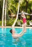 Padre activo que enseña a su hija del niño a nadar en piscina en centro turístico tropical en Tailandia, Phuket Fotos de archivo libres de regalías