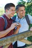 Padre With Adult Son en paseo en campo con los prismáticos Fotos de archivo libres de regalías