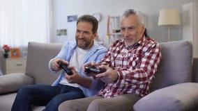Padre adulto e figlio che giocano video gioco divertendosi insieme, attività di svago video d archivio
