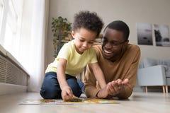 Padre africano e poco figlio raccogliere puzzle a casa immagini stock libere da diritti