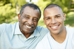 Padre afroamericano And Adult Son que se relaja en parque Foto de archivo libre de regalías