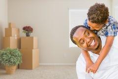 Padre afroamericano e figlio della corsa mista nella sala con la m. imballata immagini stock