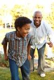 Padre afroamericano e hijo que juegan y que ríen Imagenes de archivo