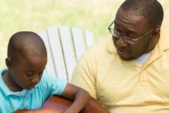 Padre afroamericano e hijo que tocan la guitarra imágenes de archivo libres de regalías