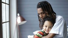 Padre afroamericano que abraza a su pequeño hijo metrajes