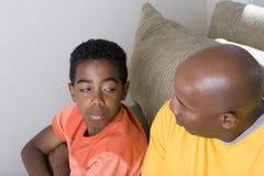 Padre afroamericano que tiene dificultad parenting su hijo Imagenes de archivo