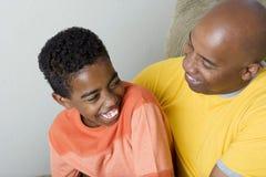 Padre afroamericano que tiene dificultad parenting su hijo Foto de archivo