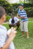 Padre afroamericano y hijos que juegan a béisbol imagen de archivo libre de regalías
