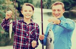 Padre alegre con el hijo que mira pescados en el gancho Fotografía de archivo