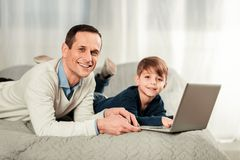 Padre alegre e hijo felices que le miran fotografía de archivo