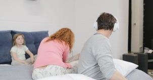 Padre alegre Listening To Music que usa los auriculares sobre la madre que calma al hijo triste en familia del dormitorio así com metrajes