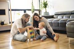 Padre alegre que juega con su bebé en piso en la sala de estar fotografía de archivo
