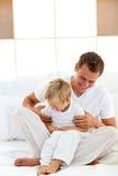 Padre alegre que juega con su muchacho en una cama Foto de archivo libre de regalías