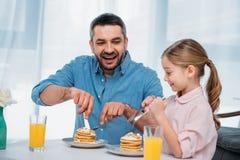 padre alegre y pequeña hija que desayunan Fotos de archivo