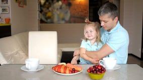 Padre alegre y su hija que desayunan junto en la cocina metrajes